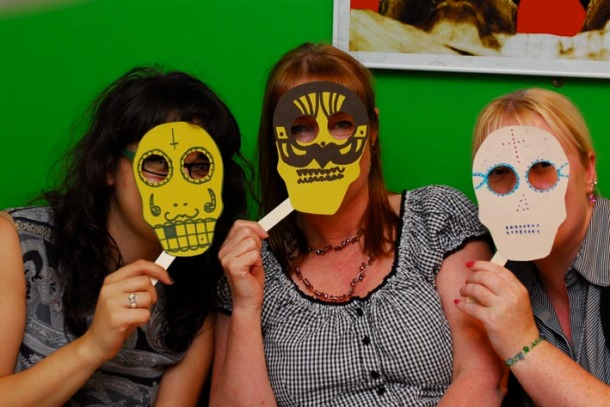 Posing with some masks made by the artist, image by Mihono Sato