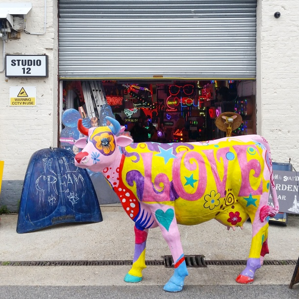 2. God's Own Junkyard - cow at the entrance