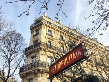 Call Me Katie - Instagramable Spots in Paris - Metro sign with a Parisian building in the background