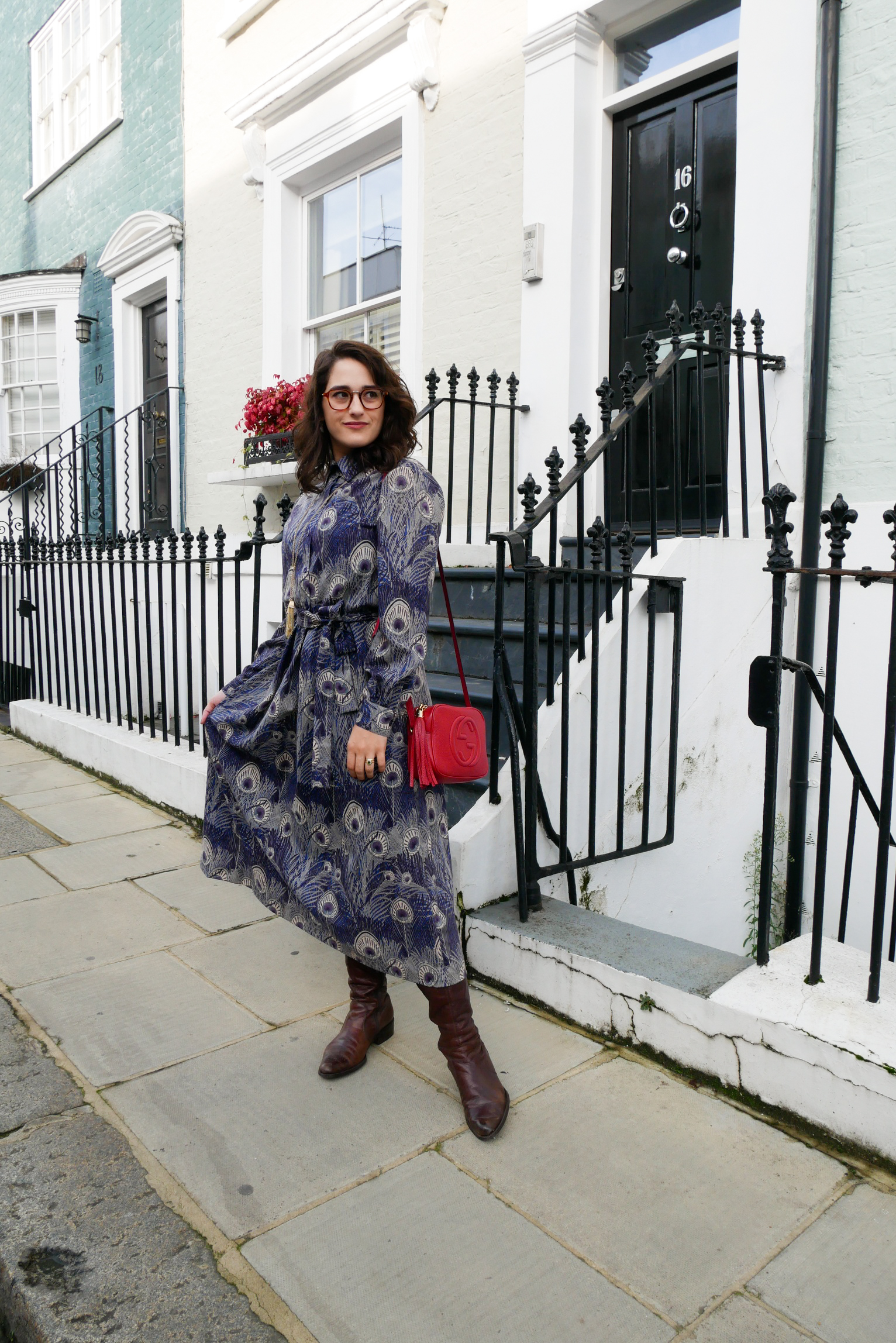 Katie wears a purple and blue peacock print midi length shirt dress with calf high brown boots, a red shoulder bag and gold tone tassel necklace on one of Notting Hill's rainbow house-front streets.