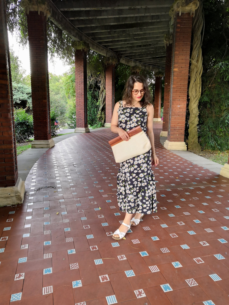 Katie wears a maxi dress with a daisy print and chains on the straps, white sandals and a cream cotton and wooden handled clutch bag. She's posing in a Spanish park.