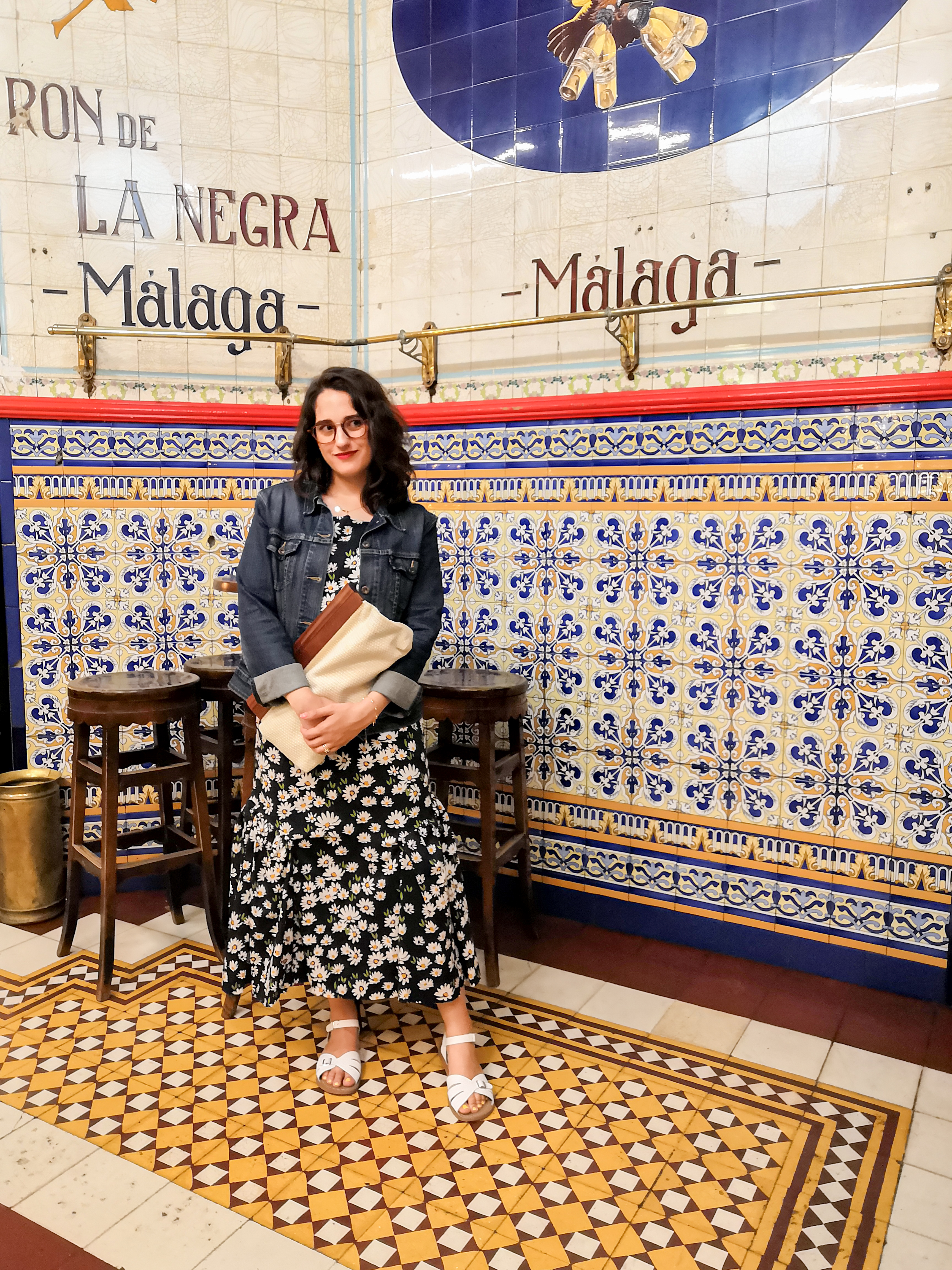 Katie wears a maxi dress with a daisy print and chains on the straps, white sandals,  a cream cotton and wooden handled clutch bag and a denim jacket with cuffed sleeves. She's standing in a Spanish bar with tiled floors and walls.