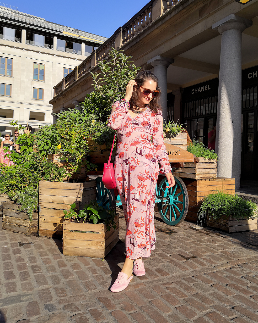 Katie wears a pink maxi dress with fuschia flowers and brown monkeys printed on. She's also wearing oversized amber coloured cat eye sunglasses, a layered multicoloured pink bugle bead necklace and bangles in the traditional Pakistan craft style.