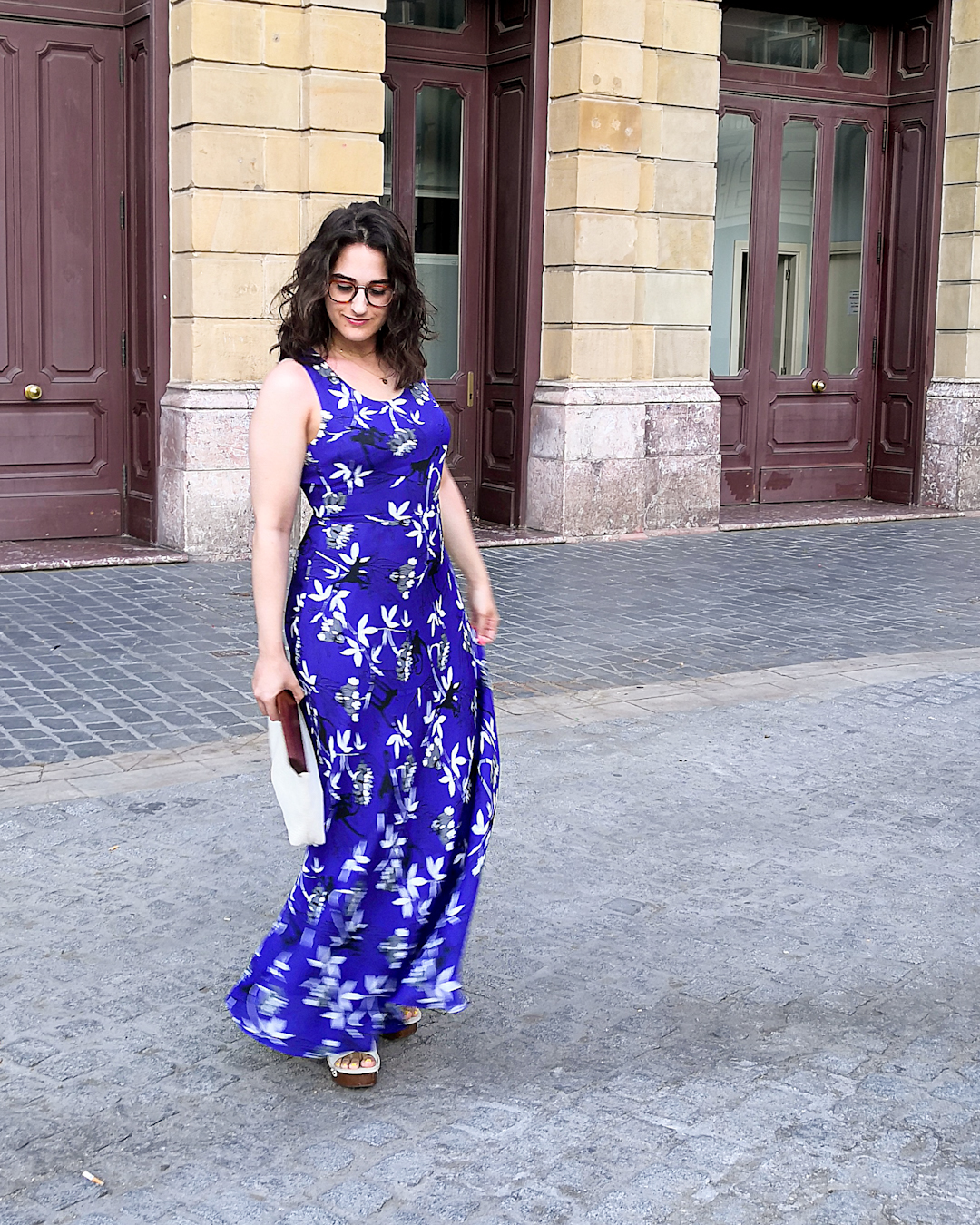 Katie wears a dark blue sleeveless maxi dress with a monkey and palm tree print. She's holding a white cotton clutch bag with a wooden handle, and wooden platform sandals with a cream leather upper. She's standing on a side street in Bilbao with a large old building behind her.
