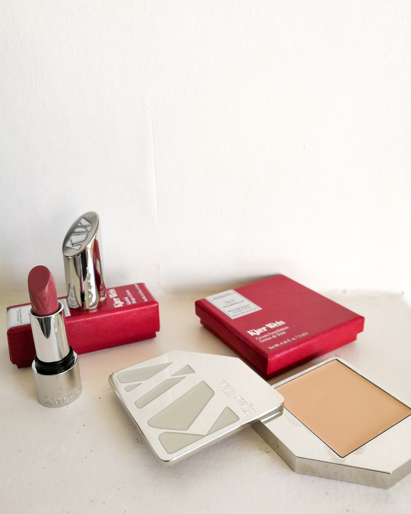 Kjaer Weiss refillable lipstick and foundation in metal containers.