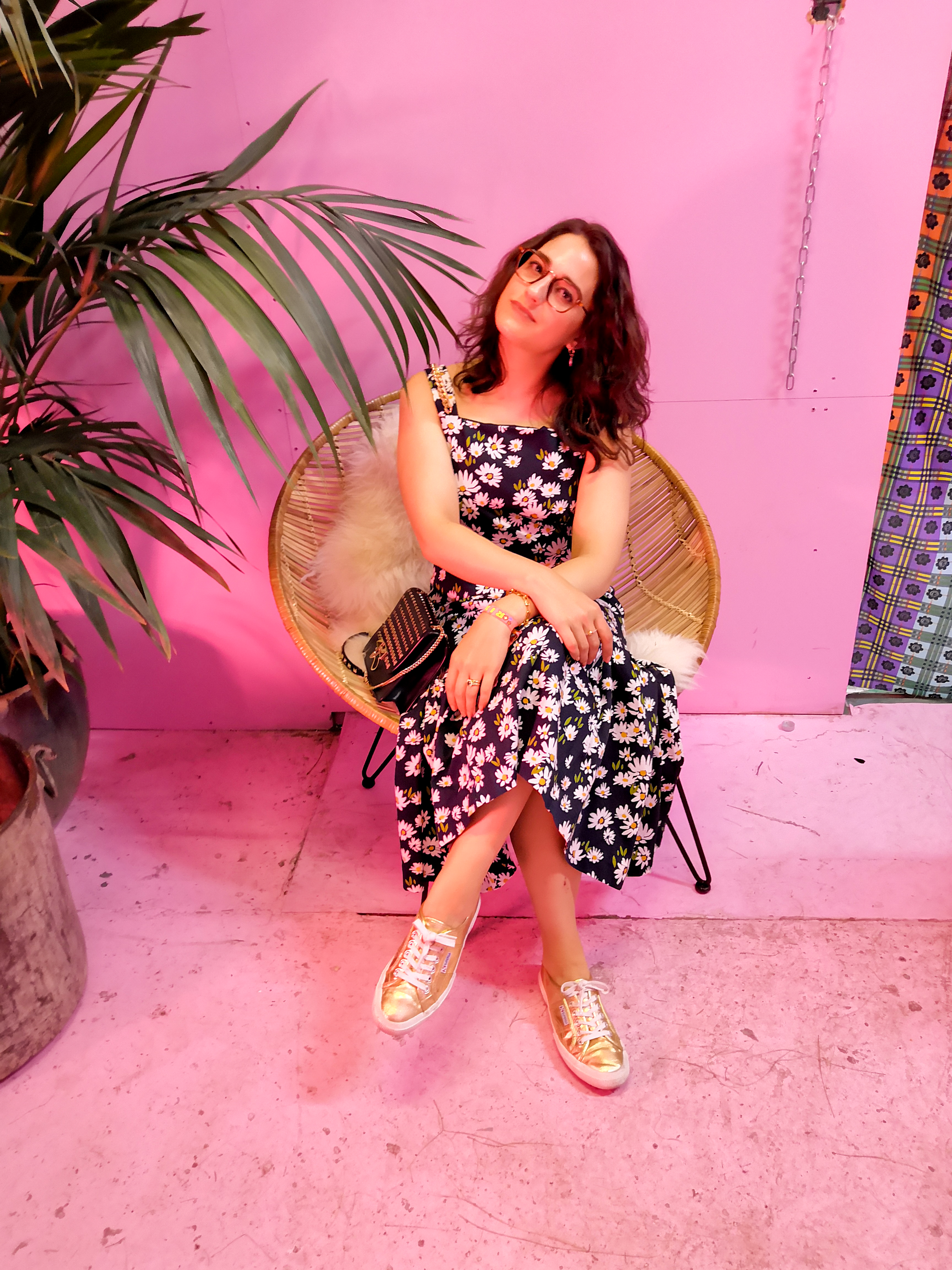 Katie wears a black and white floral maxi dress. She sits on a wicker chair next to a large potted plant in a room with pink walls.