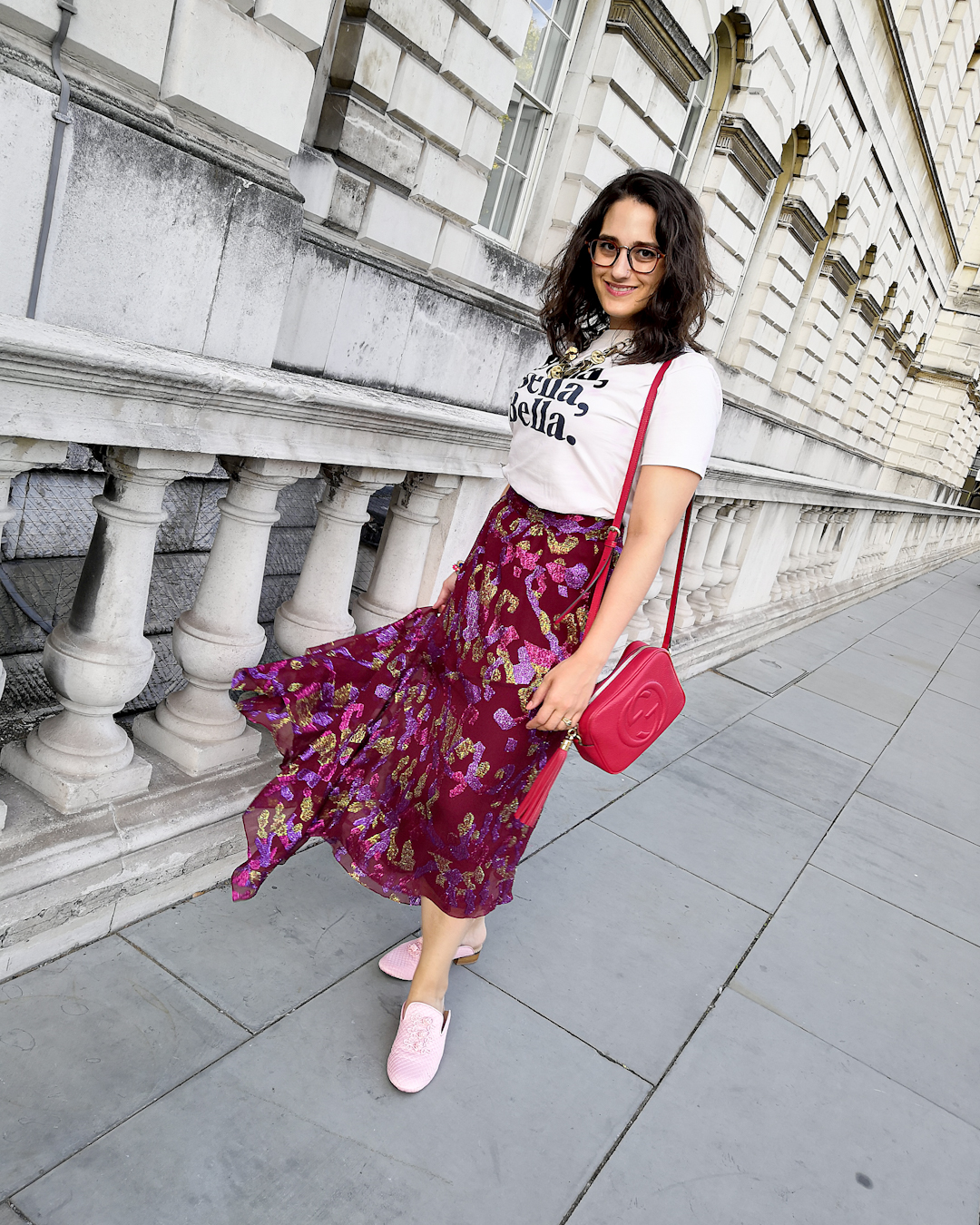 "Katie wears a cream T shirt with the words ""Bella Bella Bella"" printed in navy serif font, an assymeyric cranberry maxi skirt with a green, purple and fuschia metallic print, and slip on pink shoes. She's accessorised with a brass layered necklace and multi colour Pakistani bangles."