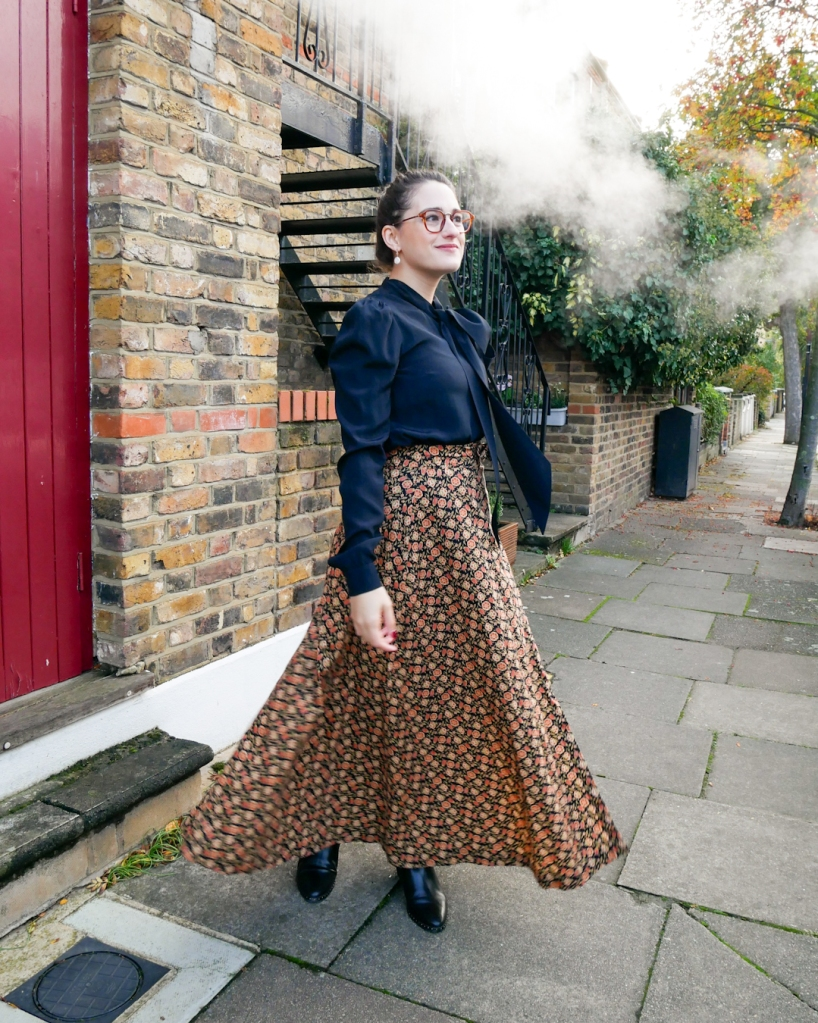 Katie wears a silky black blouse with long sleeves and a pussybow at the neck, matched with an autumnal coloured maxi skirt with ditsy floral print and black ankle boots.