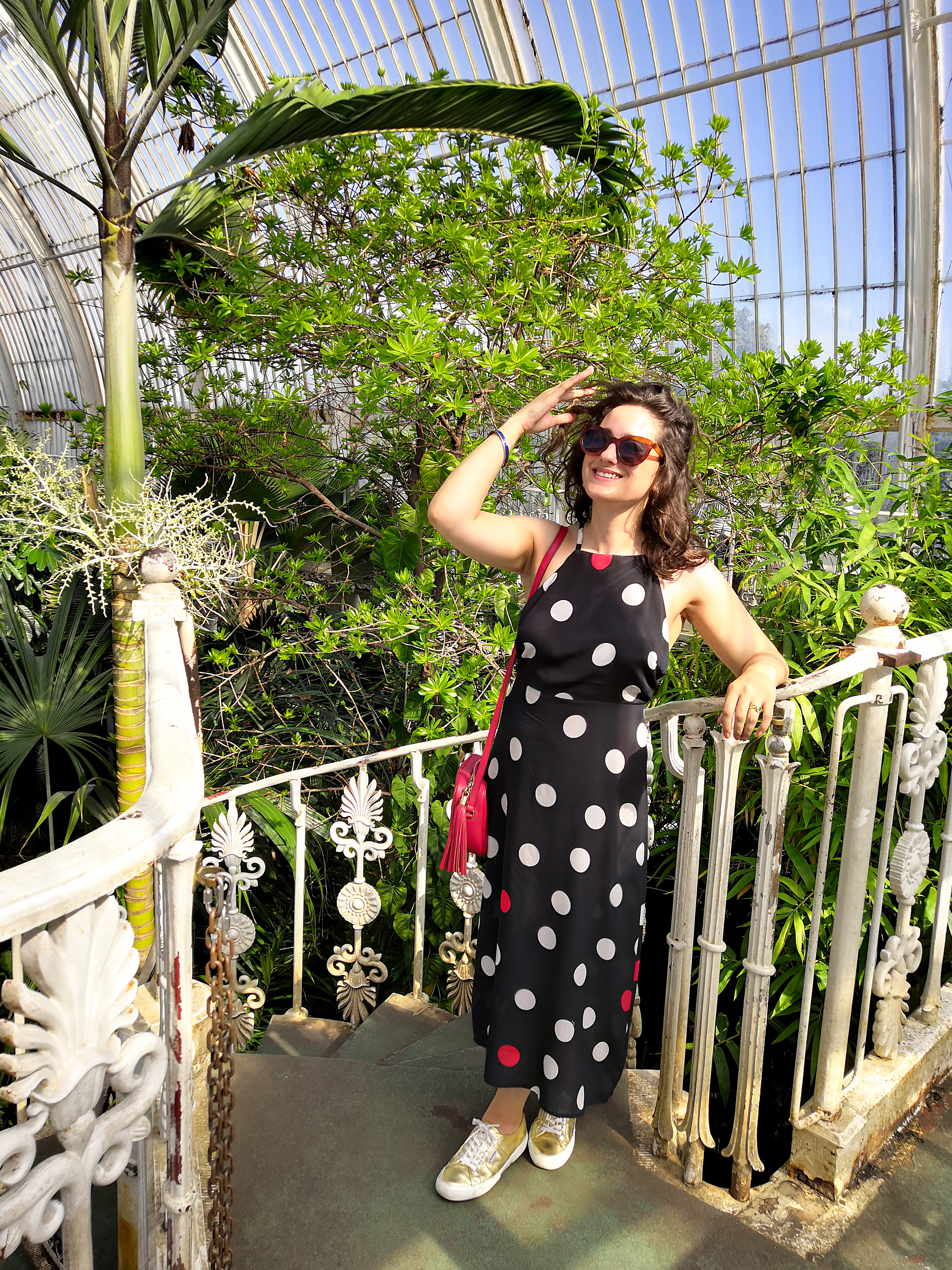Katie is wearing a navy, white and red statement polkadot maxi dress with spaghetti straps and an open back. The photos have been taken in Kew Gardens on a sunny day and she's surrounded by plants.
