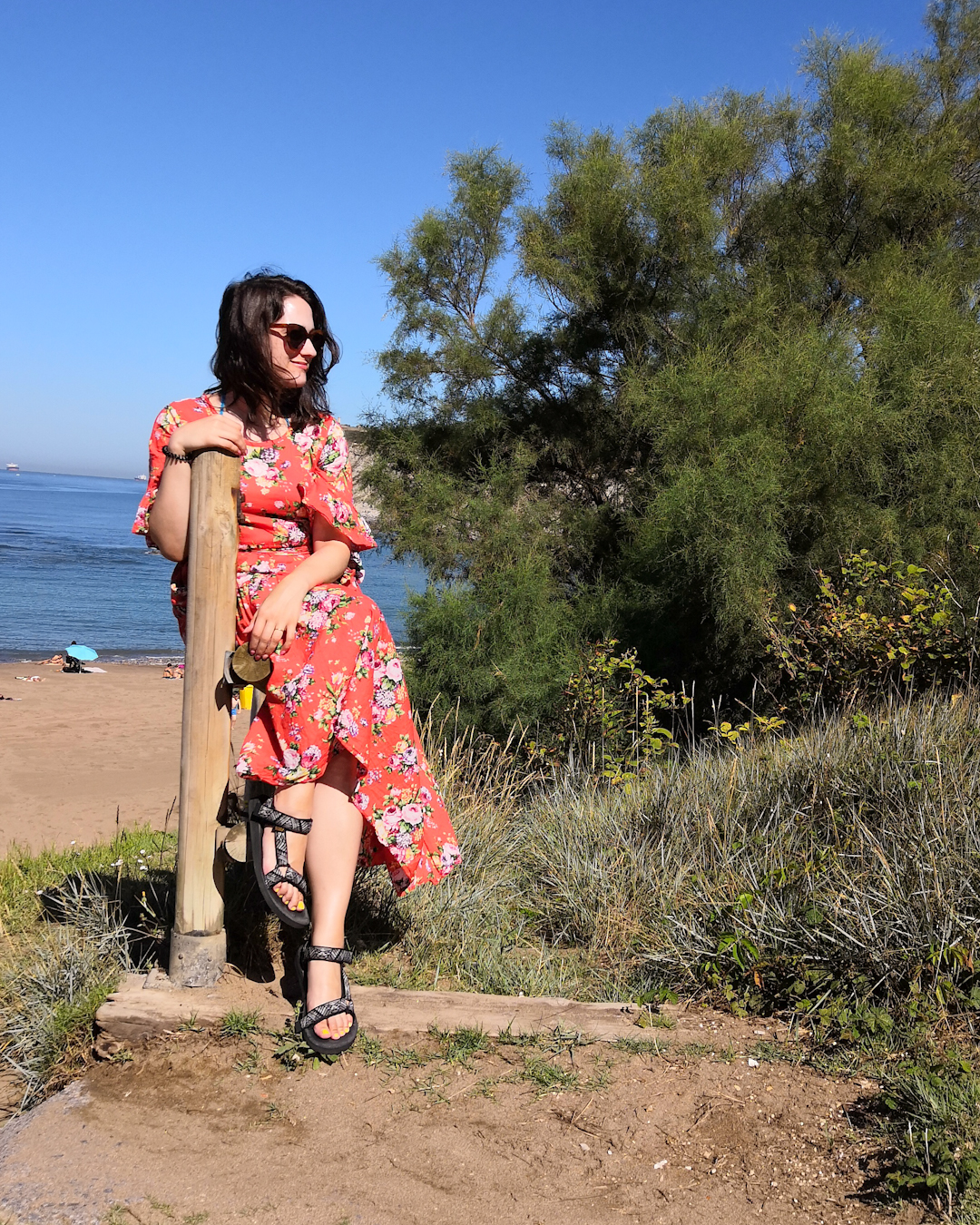 Katie is at the beach. She wears sunglasses & an orange maxi dress with floral pattern & tiered hem. She sits on a wooden rail leading to the beach, the sea is behind her.