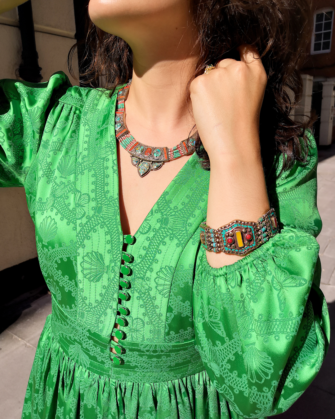 Katie wears a green dress with long poofy sleeves, a nipped in waist and short flouncy skirt. She's carrying a red shoulder bag and wearing pink slip on flats, and has accessorised with Berber style jewellery.