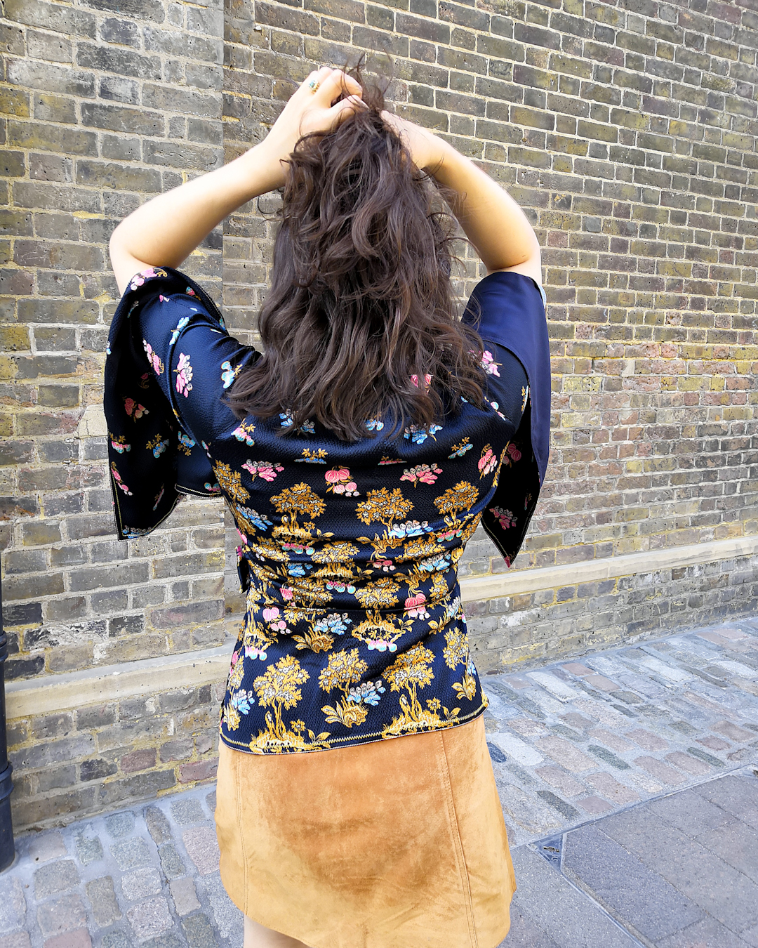 Katie wears a wrap top with a navy, pink and goldenrod floral pattern, a suede tan button up mini skirt and lace up black boots with sunglasses in front of a brick wall.