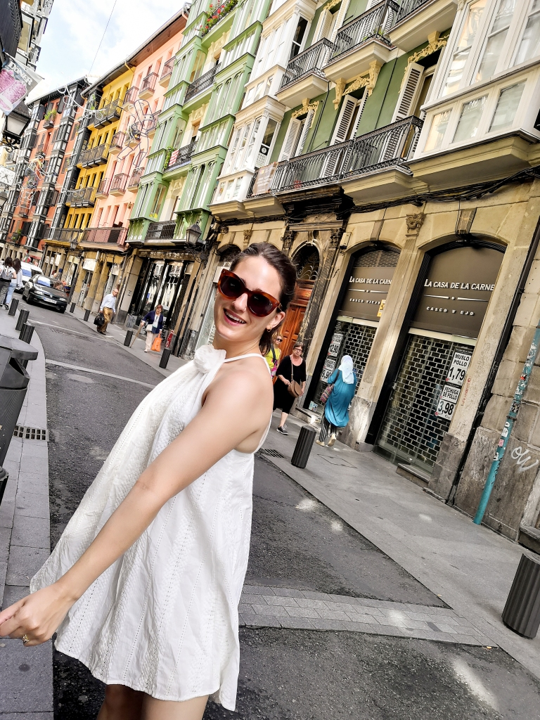 Walking along the cobbled streets of the old city in Bilbao. Katie wears her hair pulled back and oversized sunglasses with a white halterneck swing dress and white sandals.