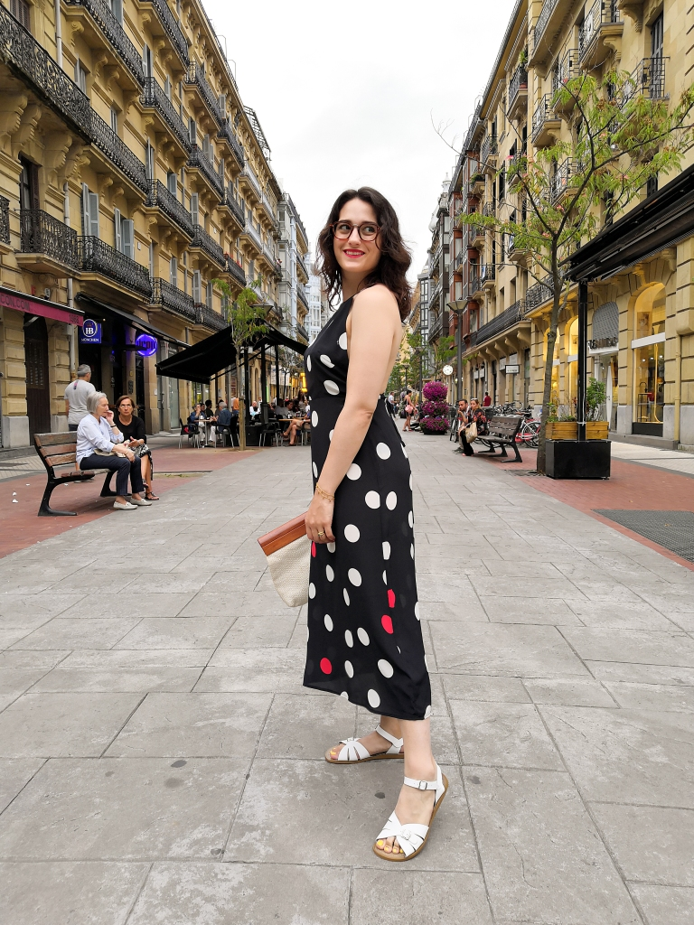 Katie walks towards the camera down a pedestrianised street in Donastia. She's wearing a halter top maxi dress with large polka dots, white sandals, a wood and whiten woven clutch bag and has bright red lipstick.