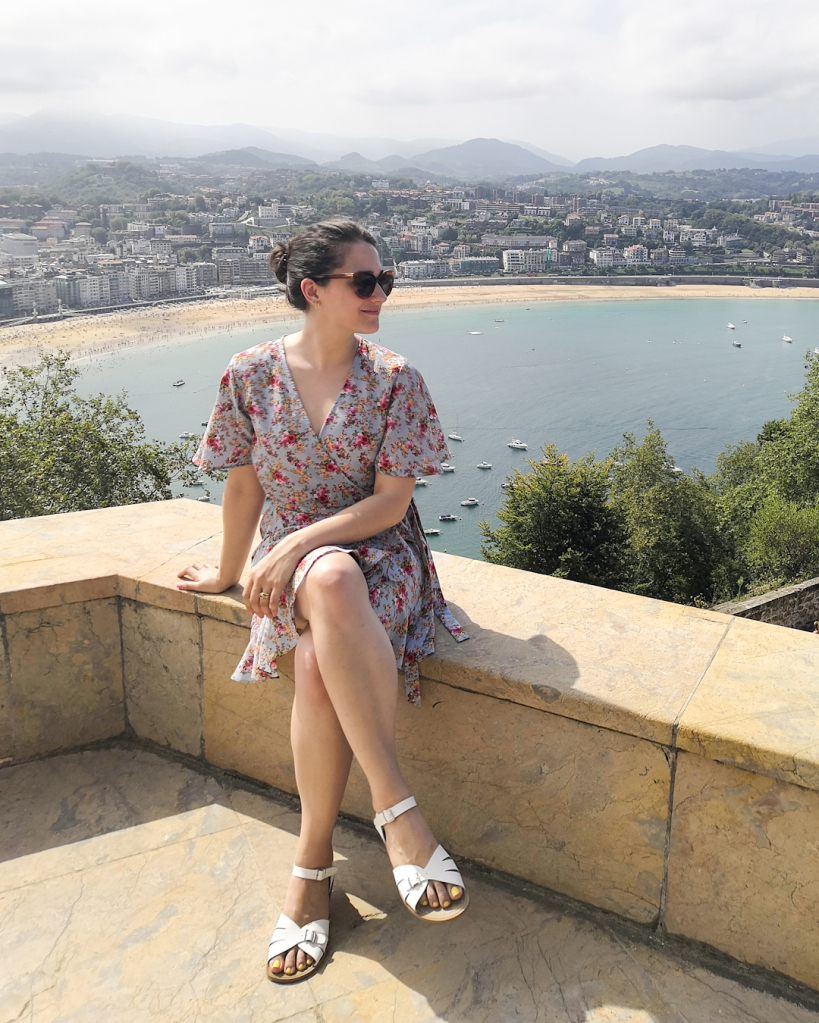 In Donasti on Monte Urgull, Katie sits on a viewing point looking out to the see with her face in profile. Her hair is back and she wears a blue floral wrap dress and white sandals. In the 2nd and 3rd pictures she wears the same outfit at the beach with her hair down.
