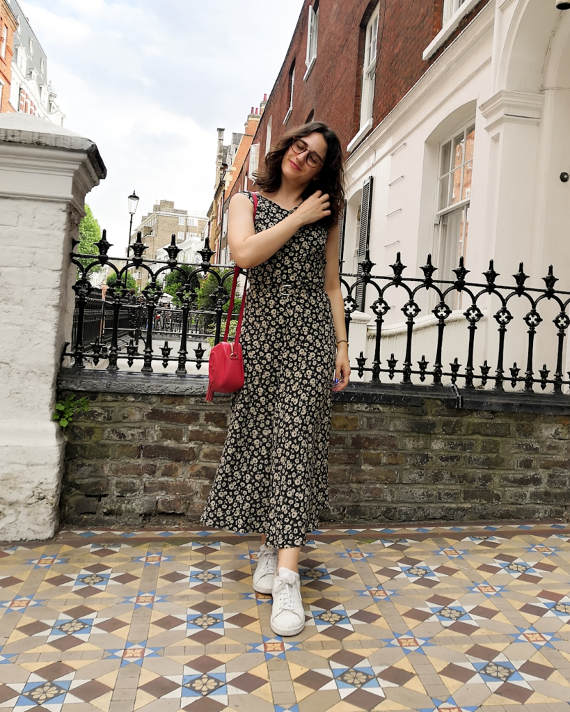 Katie wears a silk maxi dress with a black and white small floral print. It has a thin matching belt and she's paired it with a red handbag and white sneakers.