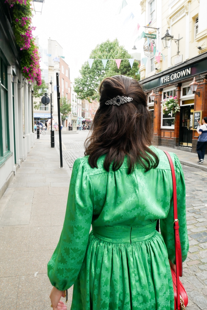 Katie is in Covent Garden, walking away from the camera She wears a green dress with long poofy sleeves, a nipped in waist and short flouncy skirt. She's carrying a red shoulder bag, and a silver and black barrette in her hair.