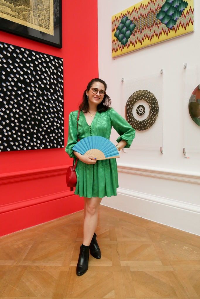 Katie is in the galleries of the Royal Academy Summer Show, where the walls and spaces are crowded with paintings, sculptures, and other artworks. She wears a green dress with long poofy sleeves, a nipped in waist and short flouncy skirt. She's carrying a red shoulder bag and a wood and blue fabric folding fan and wearing black ankle boots.