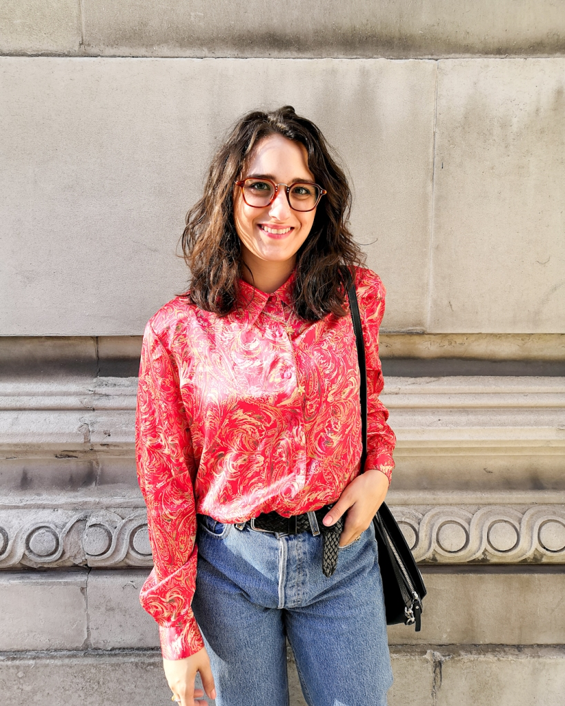 Katie wears a red and gold patterned blouse with high waisted denim cuffed above the her Dr Martens boots. Her hair is down and wavy. She's standing in front of a stone wall with minimal details.