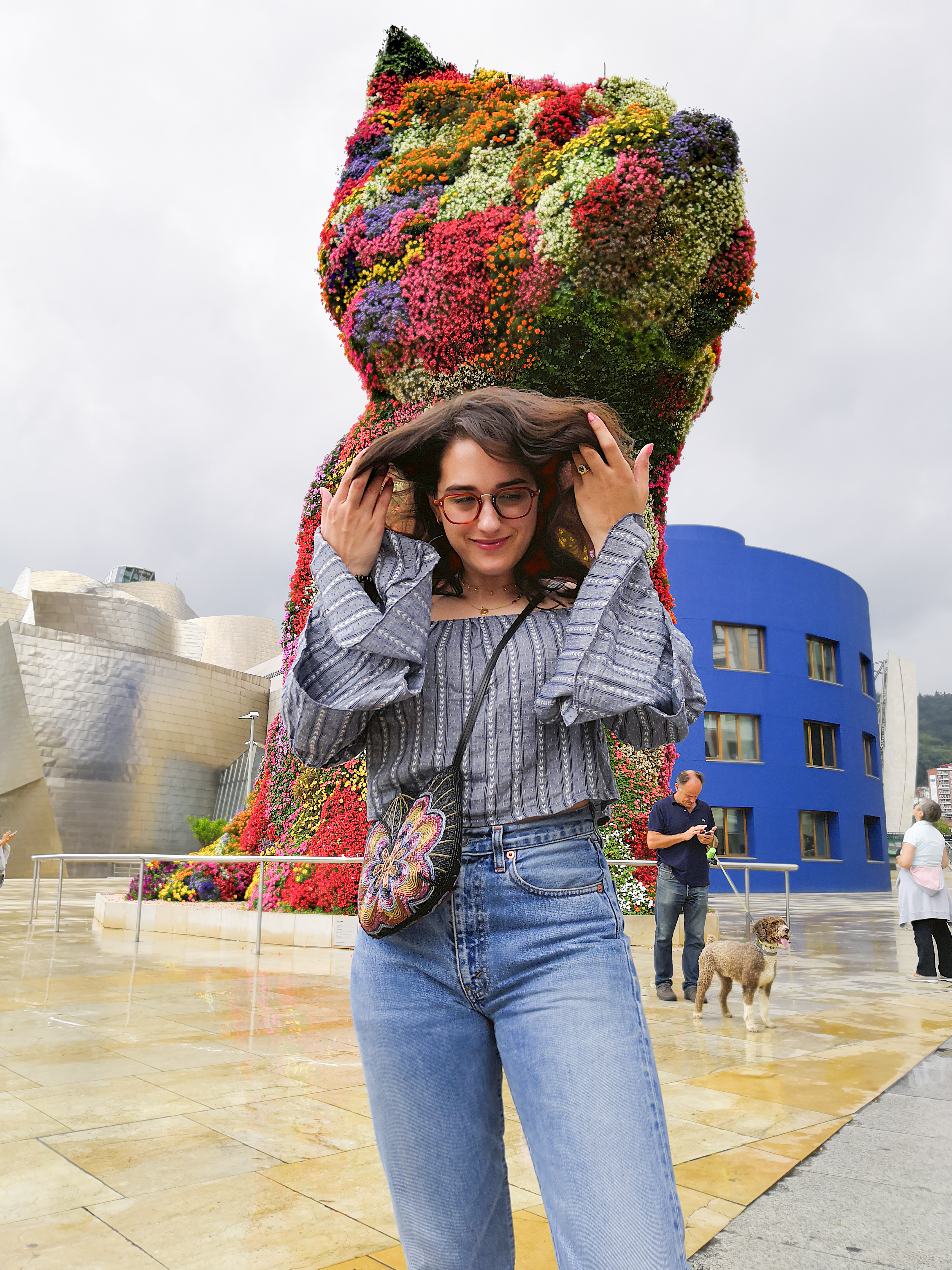 Katie is outside the Guggenheim Bilbao. She's in front of the Puppy statue. It's a drizzly day and the sky is a white / grey between showers. She wears a blue-grey off the shoulder crop top with tiered flute sleeves, high waisted jeans, white sneakers and a multicoloured beaded crossbody bag.