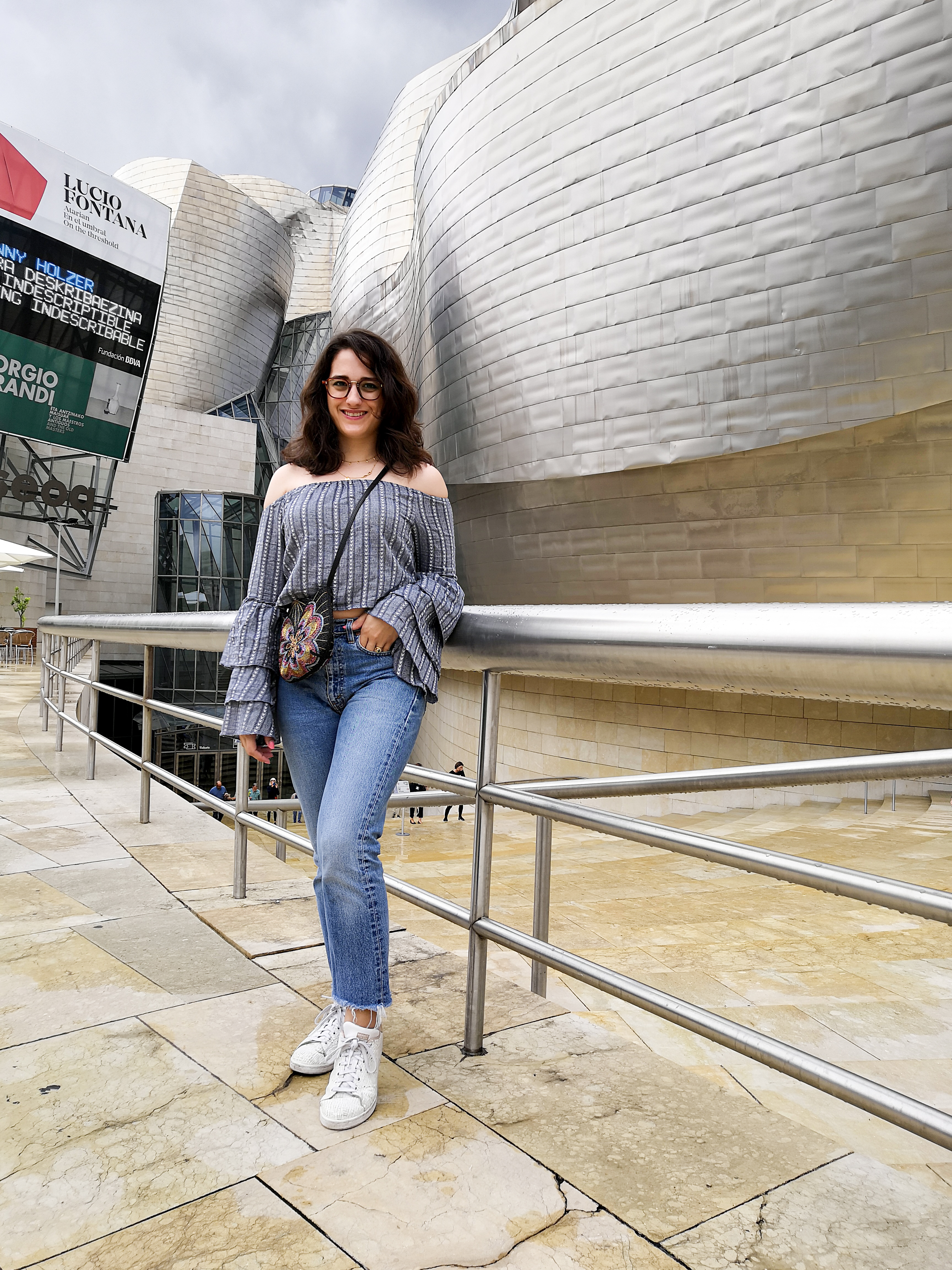 Katie is outside the Guggenheim Bilbao. She stands in front of the main entrance. It's a drizzly day and the sky is a white / grey between showers. She wears a blue-grey off the shoulder crop top with tiered flute sleeves, high waisted jeans, white sneakers and a multicoloured beaded crossbody bag.