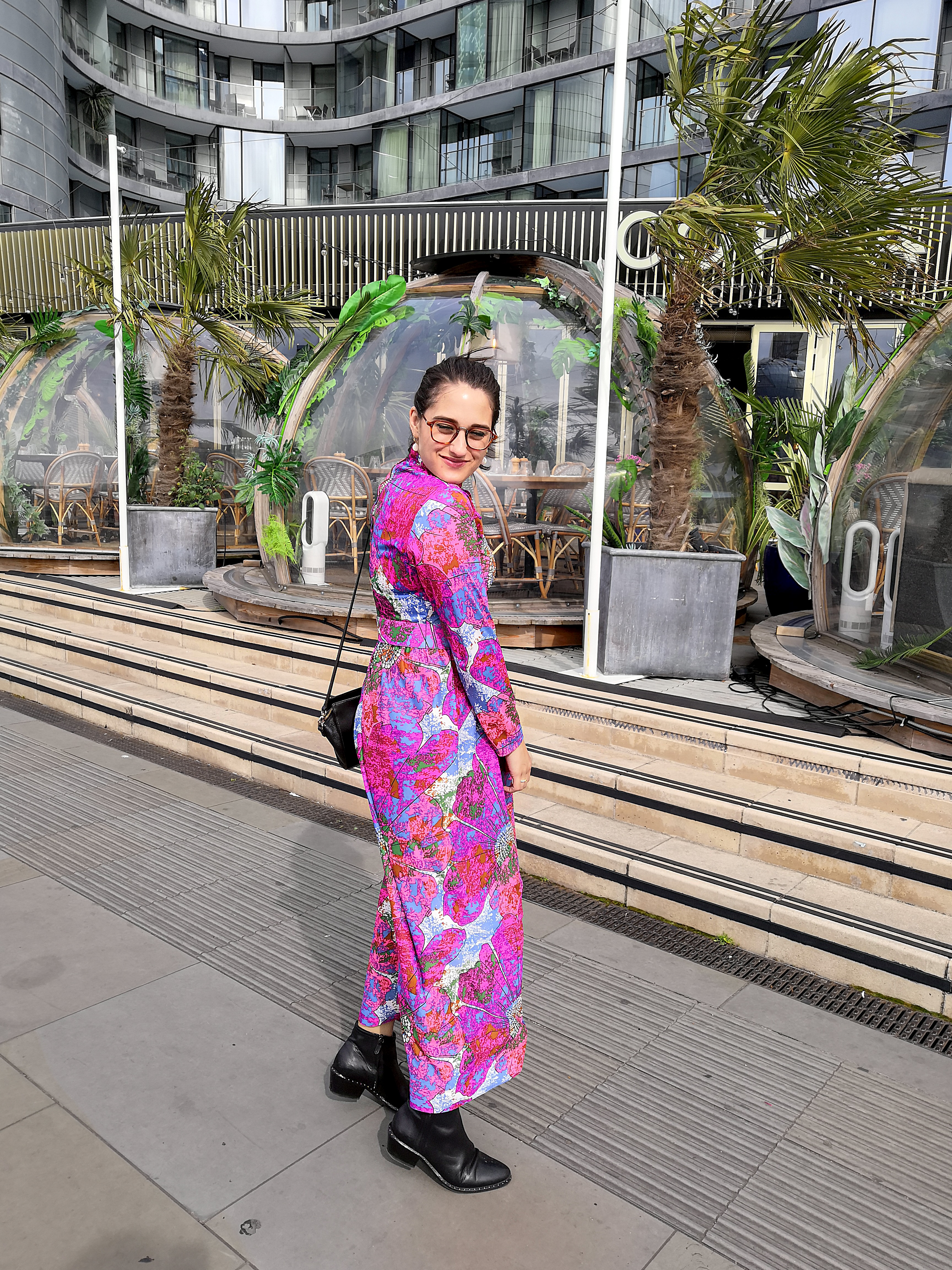 Katie wears a pink, blue and white multi colour vintage maxi dress with long sleeves, high neck, matching belt and black shoes and a small black shoulder bag. Her hair is pulled back in a pony tail and she's standing in front of the surfer shacks at Copa Club on Tower Bridge.