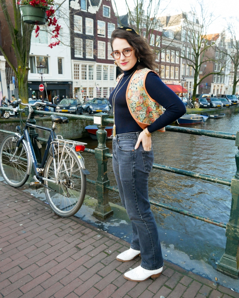 Katie is standing by an Amsterdam Canal in 9 Straats wearing a fitted knit navy roll neck layered under a vintage pastel floral waistcoat with faded black vintage Levis 501s and white cowgirl style boots. She's accessorised with large gold tone hoop earrings with mini faux pearl details, a black and gold headband, a long 1970s metal tassel necklace and red lipstick.