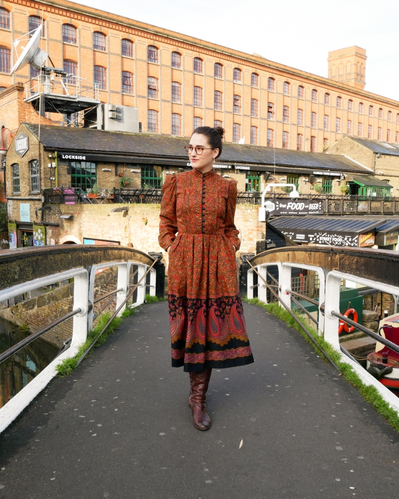 Katie wears a vintage 1970s dress with a high neck, button front to the waist, bell sleeves and A line skirt with a ditsy floral print and paisley detail at the hem in autumnal shades of orange, red, brown, blue and purple and black details.