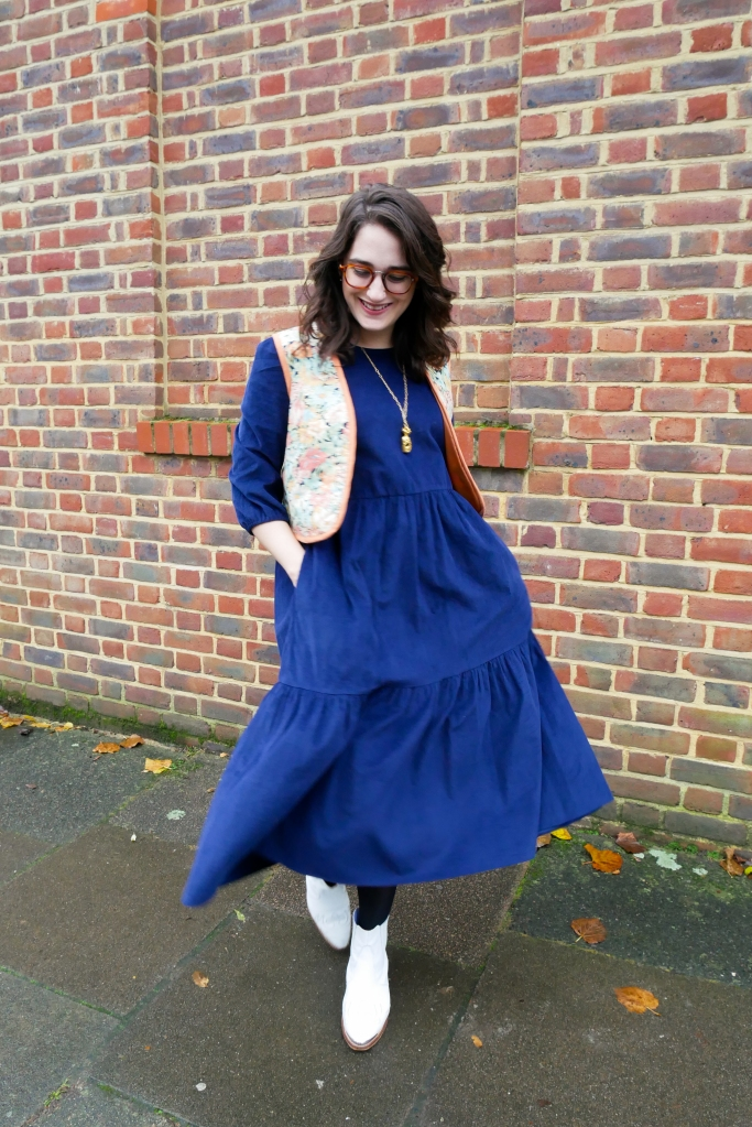 Katie wears a floaty navy courderoy midi dress with 3/4 sleeves, a vintage floral waistcoat, white boots and gold tone jewellery.