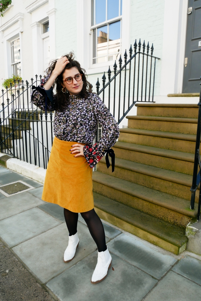 Katie wears a purple floral blouse with clashing red floral print detail at the cuffs, a mustard corduroy knee length skirt, black tights and white cowgirl style boots.